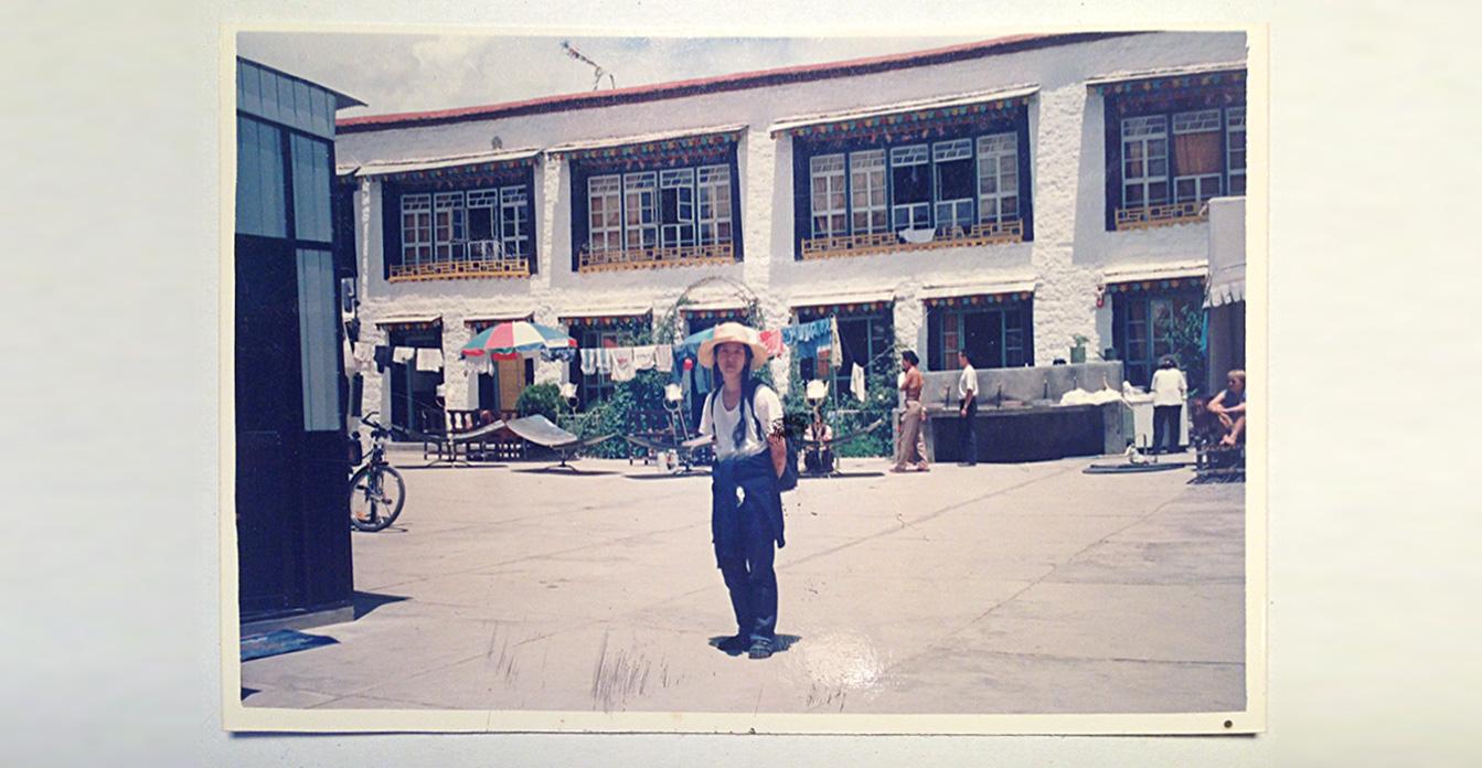Ein altes, verblichenes Foto zeigt Shau Chung Shin, die im Hof eines Hostels in Lhasa, der Hauptstadt Tibets, steht. Die Sonne steht hoch, die Schatten sind klein. Sie trägt einen Strohhut, ein weißes T-Shirt und lange Zöpfe. Sie hat die Arme hinter ihrem Rücken verschränkt.