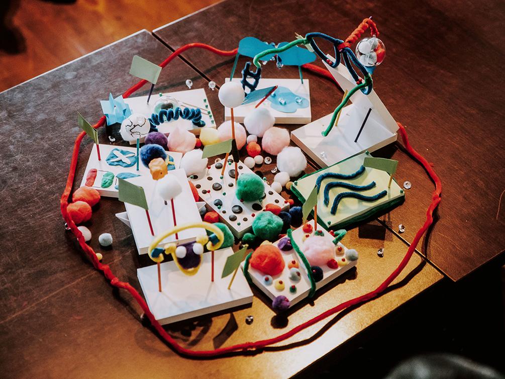 Ein Gefüge aus mehreren bunten Modellen, die zusammengelegt wurden und von einem Kreis aus roten Pfeifenreinigern umgeben sind.