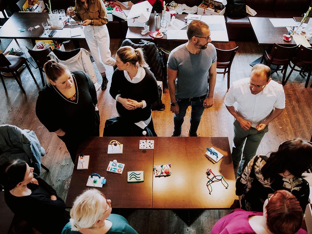 Workshop-Teilnehmer stehen um einen Tisch herum worauf 9 Modelle platziert sind.