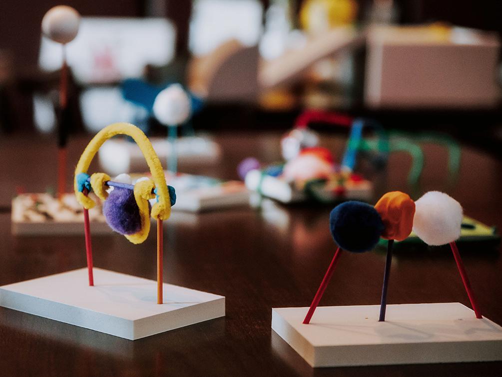 Nahansicht von zwei bunten Modellen, die auf einem braunen Tisch stehen. Im Hintergrund sind weitere Modelle unscharf zu erkennen.